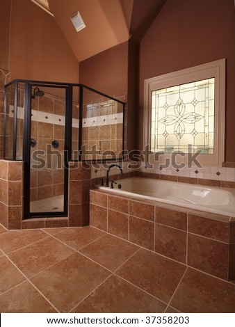 Luxury Home Tile Bathroom with stained glass window and tub - stock photo