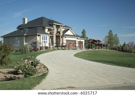 Luxury home with large driveway and landscaping - stock photo