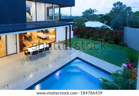 Luxury home with swimming pool at dusk - stock photo