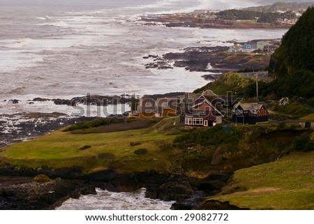 Luxury homes along a rock pacific northwest shoreline. - stock photo