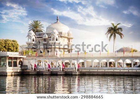 Luxury hotel on the Pichola lake at blue cloudy sky in Udaipur, Rajasthan, India - stock photo