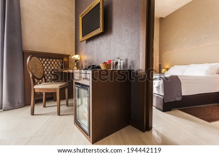Luxury hotel room interior with mini bar in brown tones - stock photo