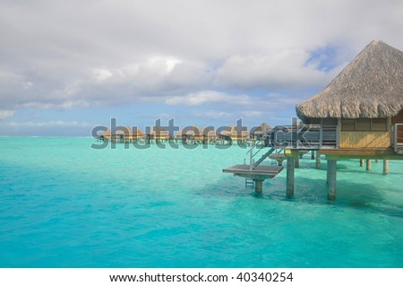 Luxury hotel suites located above the blue lagoon in Bora Bora, Tahiti. - stock photo