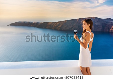 Luxury hotel terrace. Europe destination summer vacation. Asian woman drinking red wine relaxing enjoying view of the mediterranean sea in Oia, Santorini, Greece. Honeymoon high end travel holiday.