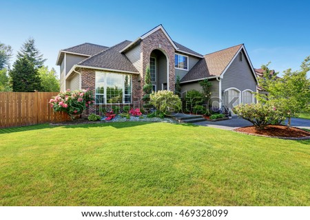 luxury house exterior with brick and siding trim and double garage well kept garden around