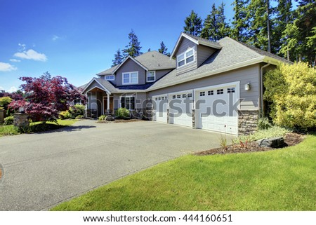 Luxury house exterior with french windows and with three car garage. - stock photo