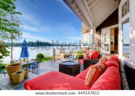 Luxury house exterior with impressive water view, cozy patio area and sitting place with wicker sofa and red pillows. - stock photo