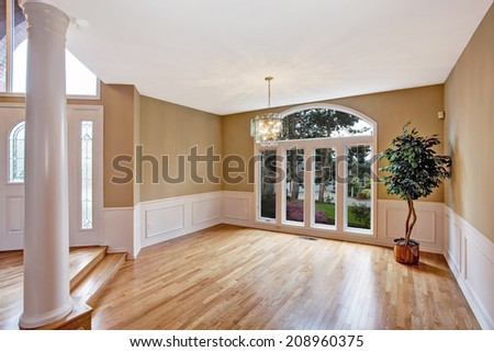 Luxury house interior. Bright  empty hallway with large window and column. Decorated with fake tree in corner - stock photo