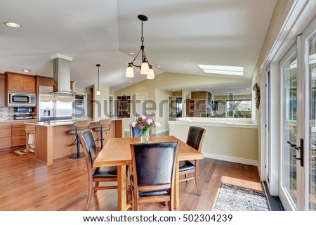 Luxury house interior with open floor plan, dining area and modern kitchen room with vaulted ceiling . Northwest, USA