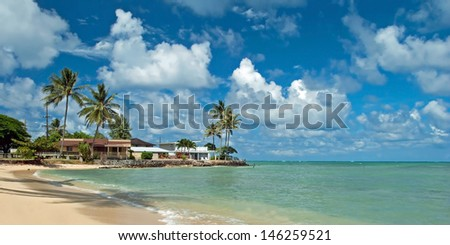 Luxury house on untouched sandy beach with palms trees and azure ocean in background panorama - stock photo