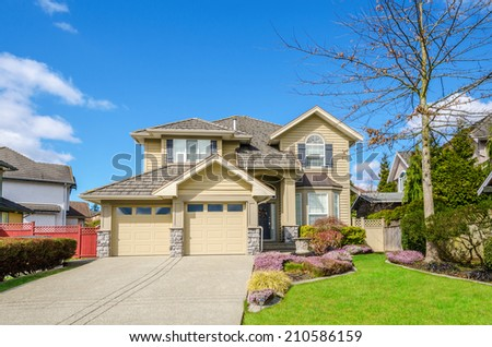 Luxury house with a two-car garage and beautiful landscaping on a sunny day. - stock photo