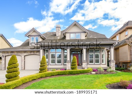 Luxury house with a two-car garage and beautiful landscaping on a sunny day in Vancouver, Canada. - stock photo
