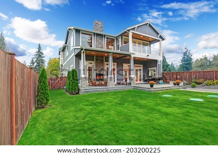 Luxury house with backyard walkout deck and column porch. View of lawn with trees and flower pots - stock photo