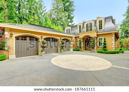 Luxury house with beautiful curb appeal. View of three car garage and driveway - stock photo