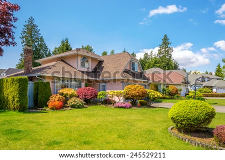 Luxury house with beautiful landscaping on a sunny day. Home exterior. - stock photo