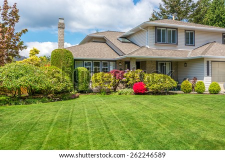 Luxury house with freshly mown grass lawn. Home exterior. - stock photo