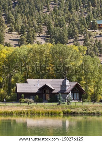 Luxury house with lake in Rocky Mountains. - stock photo
