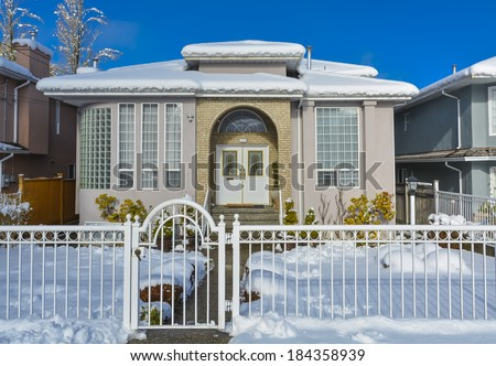 Luxury house with metal fence in front and blue sky background. Luxury family house on winter season with closed entrance gate in front. - stock photo