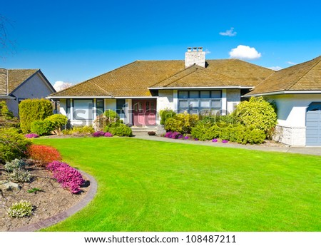 Luxury house with nicely landscaped front yard. - stock photo