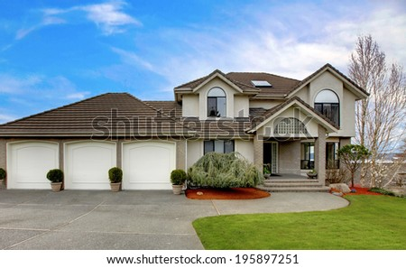 Luxury house with three car garage and porch view. - stock photo