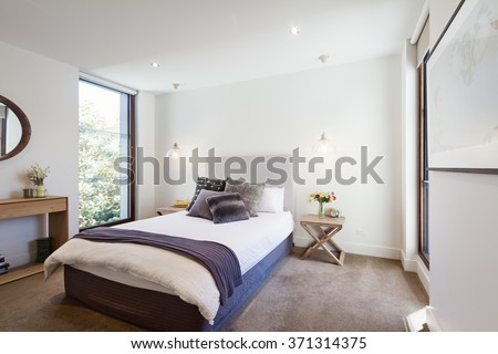 Luxury interior designed bedroom with comfy pillows and throw rug and pendant lights - stock photo