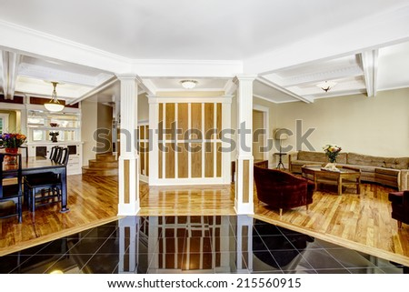 Luxury interior. Foyer with black shiny tile floor, columns and coffered ceiling system. Brown wall with white trim blend perfectly with hardwood floor - stock photo