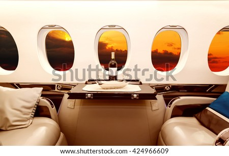 Luxury interior in bright colors of genuine leather in the business jet, sky, clouds and sunset through the porthole - stock photo