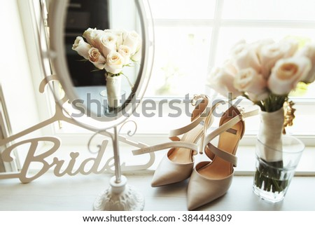 Luxury ivory shoes and bride jewel on the table - stock photo