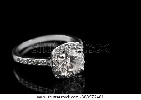 Luxury jewellery. White gold or silver engagement ring with diamonds closeup on black glass background. Selective focus. - stock photo