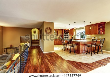 Luxury kitchen connected to living room. Kitchen with tile floor, stained cabinets and granite counter top