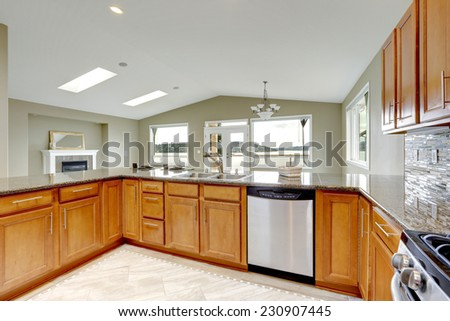 Luxury kitchen room with bright brown cabinets and built-in appliances - stock photo