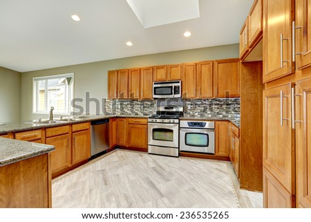 Luxury kitchen room with bright brown cabinets, mosaic backsplash trim and steel appliances. - stock photo