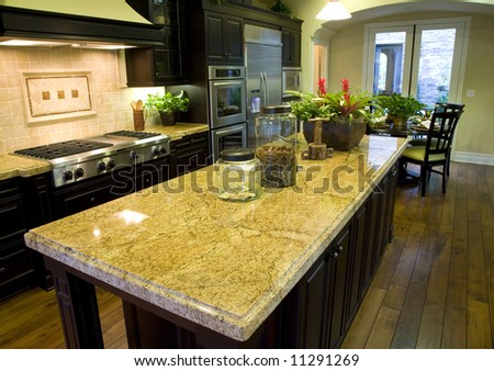 Luxury kitchen with a hardwood floor and granite island.