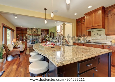 Luxury kitchen with bar style island, and hardwood floor. - stock photo