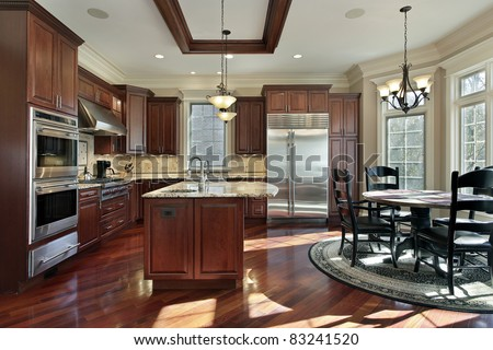 Luxury kitchen with cherry wood cabinetry and eating area - stock photo