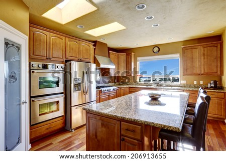Luxury kitchen with SS-appliances and kitchen island with black leather chairs - stock photo