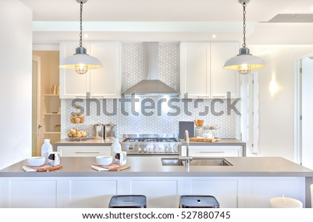 Luxury kitchen with the counter and stoves under lights near chimney