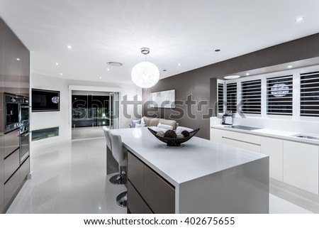 Luxury kitchen with wall oven cabinets next to the fancy items on the white counter top illuminated using round hanging lamp - stock photo