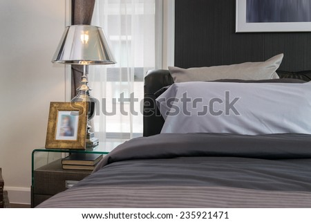luxury lamp and picture frame on bedside table in bedroom  - stock photo