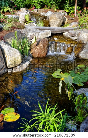 Luxury landscaped environmental garden with fancy plant landscaping and stone landscape decor around a decorative pond decorated with water lilies and stocked with koy fish under a waterfall  - stock photo