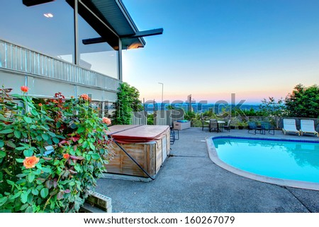Luxury large home grounds with swimming pool. Summer Northwest evening. Lake Washington view. Hot tub and house exterior.