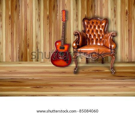 luxury leather armchair and sunburst electric guitar on wood background - stock photo