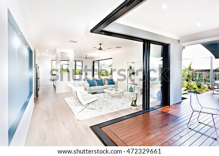 Luxury living room and wooden hallway beside a patio with white walls, the floor carpet and pillows on the sofas near the rack  fill the room with furniture