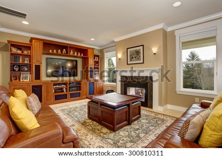 Luxury living room with stone tiled floor, including leather sofas and a fireplace. - stock photo
