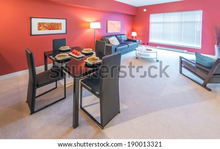 Luxury living suite : dining room with the nicely served table and red wall and living room at the back . Interior design.