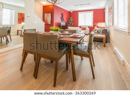 Luxury living suite: nicely decorated dining table and the kitchen at the back. Interior design. - stock photo