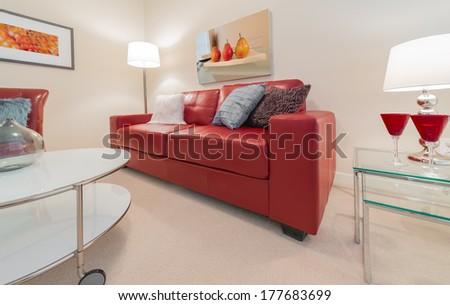 Luxury living suite of brand new house. Nicely decorated modern family, living room with red color couch, chair and coffee table. Interior design. - stock photo