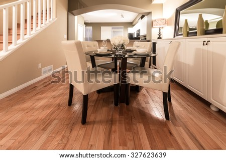 Luxury living suite with nicely decorated dining table, stylish mirror at the wall and the living room at the back.  Interior design. - stock photo