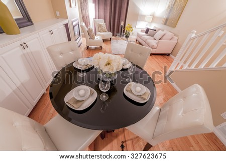 Luxury living suite with nicely decorated dining table, stylish mirror at the wall and the living room at the back . Interior design.