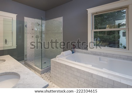 Luxury Master bathroom with Glass shower and white marble counter tops plus bath top - stock photo